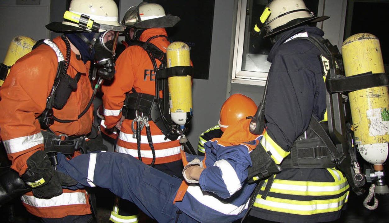 """Atemschutzträger bergen eine """"verletzte"""" Person.     Foto: Sandra Decoux-Kone"""