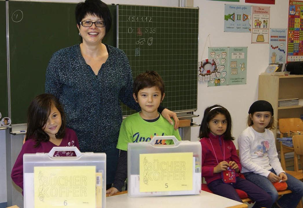 Die Leiterin der Stadtbibliothek Angel... ersten Klassen je zwei Bücherkoffer.   | Foto: Rheinschule