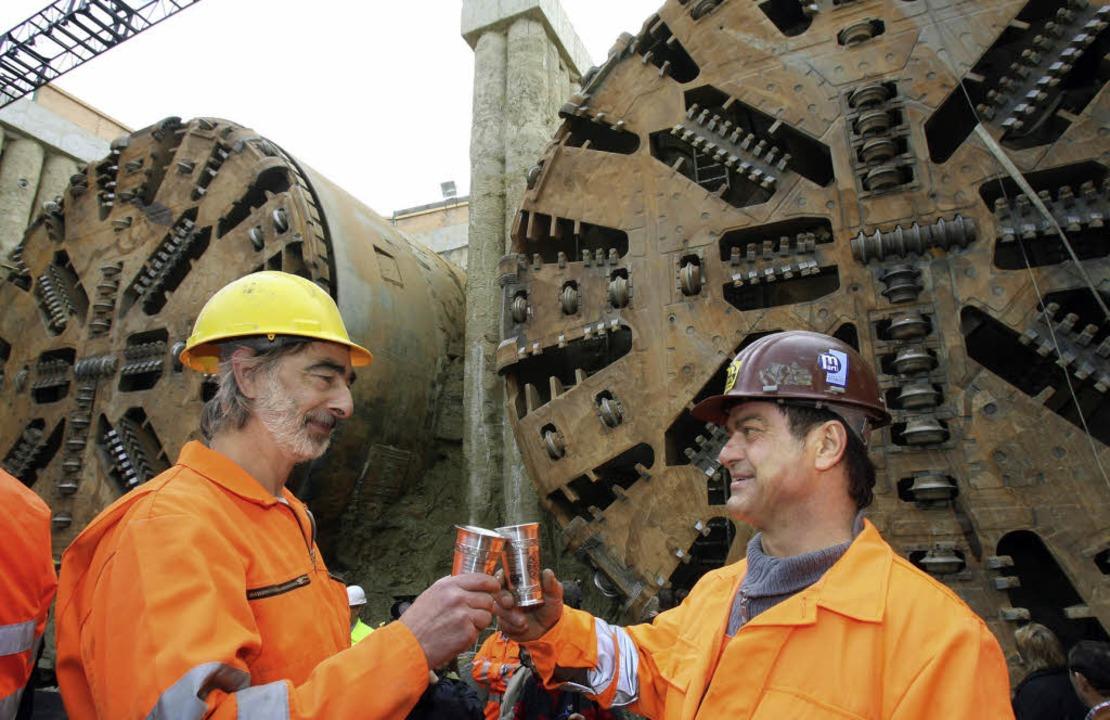 Durchbruch: Zwei Tunnelarbeiter stoßen...ber 2007 auf die gelungene Arbeit an.   | Foto: dpa