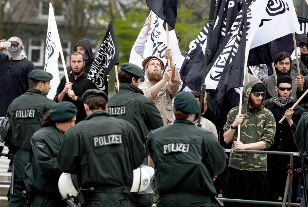 Polizisten stehen in Solingen vor protestierenden Salafisten.  | Foto: dapd
