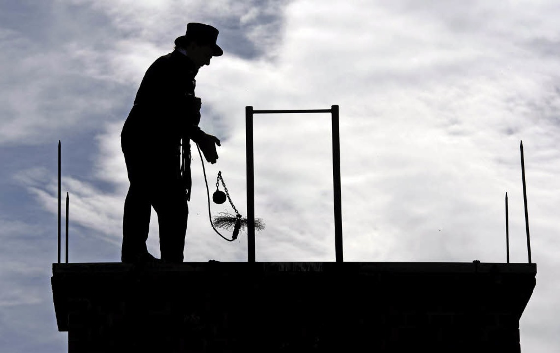Ein Kaminkehrermeister reinigt den Sch...uses mit einer Schornsteinfeger-Bürste  | Foto: DPA