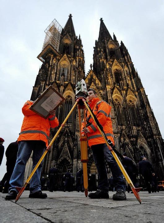 Alles noch im Lot? Vermessungstechniker vor dem Kölner Dom   | Foto: dpa