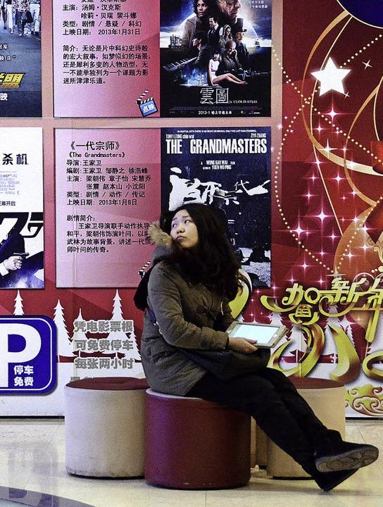Einsam und unsicher? Eine junge Chinesin sitzt in Peking im Kino.     Foto: AFP