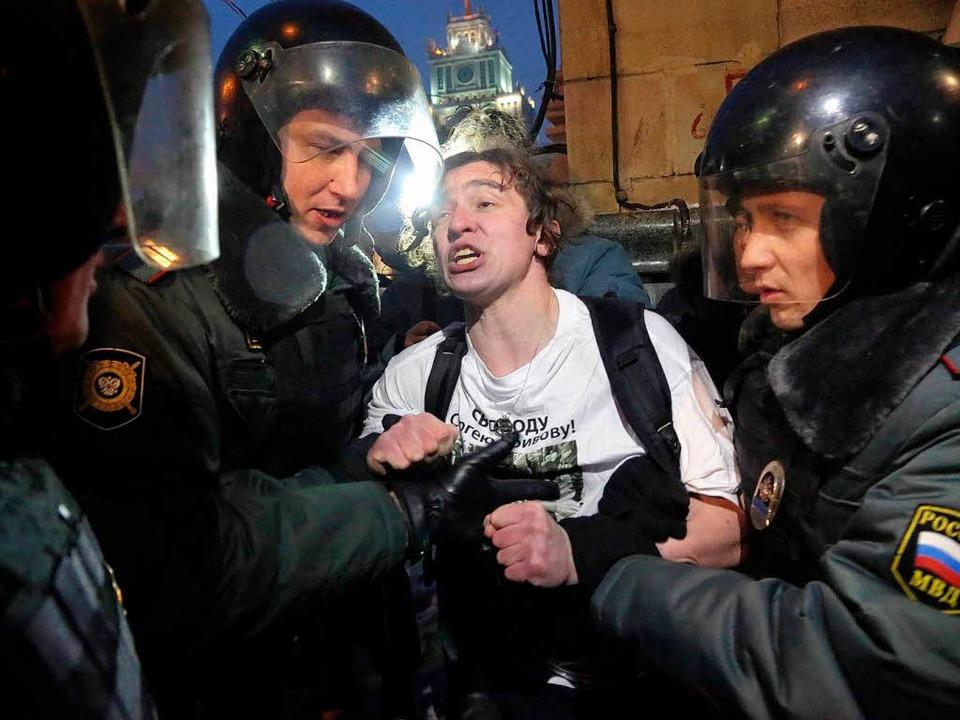 Ein Polizist nimmt in Moskau einen Demonstranten fest.   | Foto: DPA