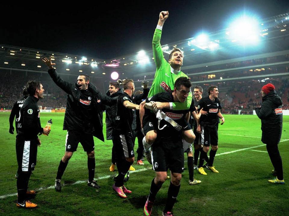 Die Freiburger bejubeln mit Torwart Oliver Baumann  den 3:2 Endstand.  | Foto: dpa