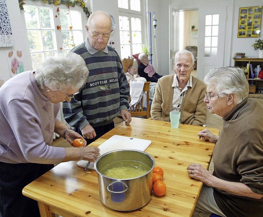 Leben Senioren gemeinsam in einer Wohn... dem Kochen gegenseitig unterstützen.     Foto: Bernd Thissen/dpa, Michael Bamberger