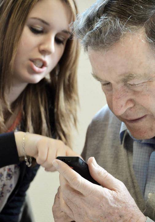 Firmandin Jana erklärt Hermann Klein die Tasten-Funktionen seines Mobiltelefons.  | Foto: Susanne Müller