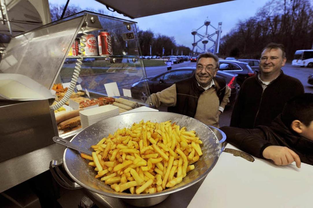 Warten auf das Leibgericht: Kunden ein...sbude in Brüssel (hinten das Atomium).  | Foto: AFP