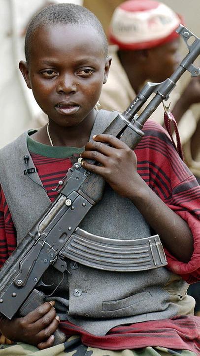 Mit einer Waffe in der Hand bewacht ei...ger Kindersoldat eine Straße im Kongo.  | Foto: DPA