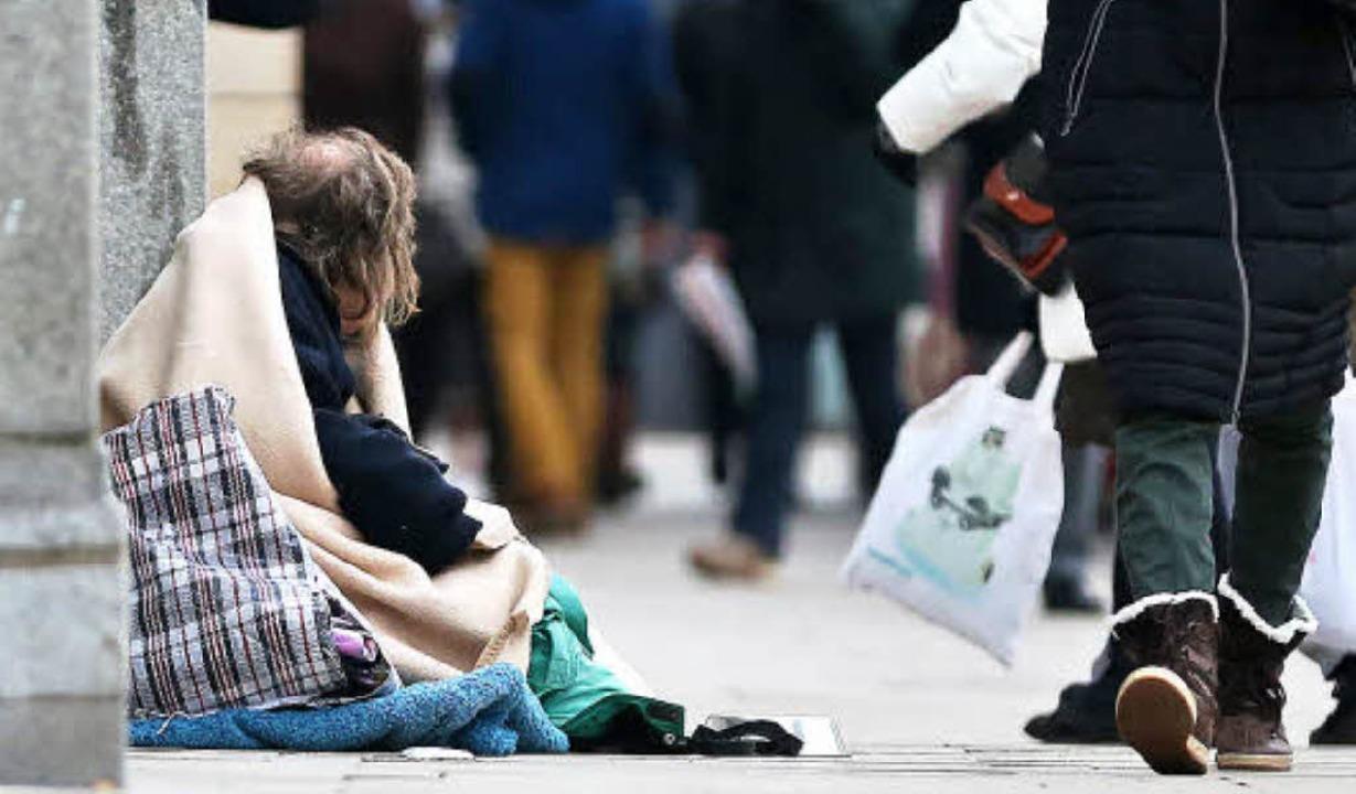 Ein Mann sitzt  in der Innenstadt von Hamburg und bittet um eine Spende.   | Foto: dpa