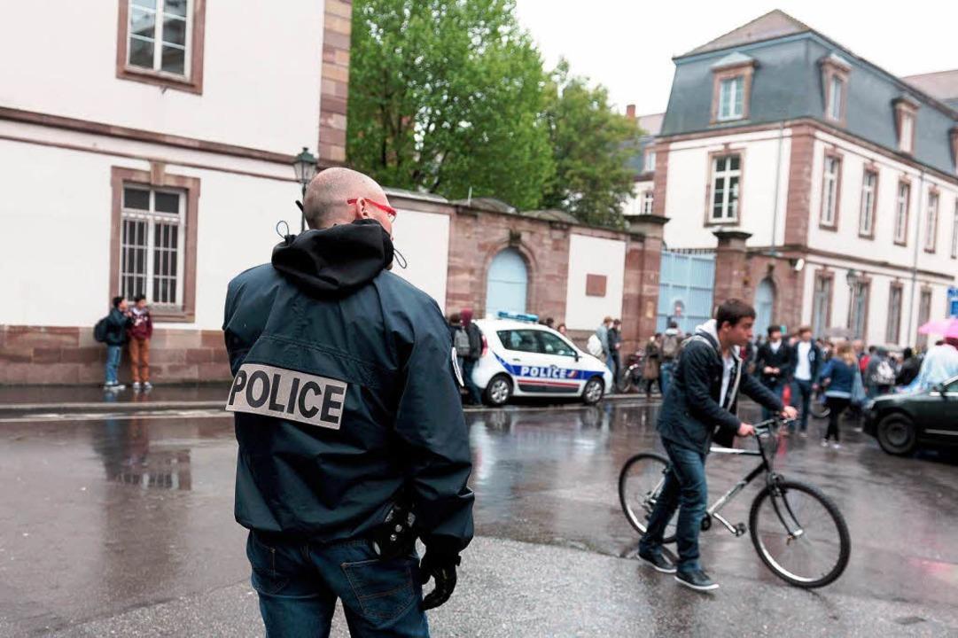 Ein Polizist bewacht den Eingang einer Straßburger Schule.   | Foto: afp
