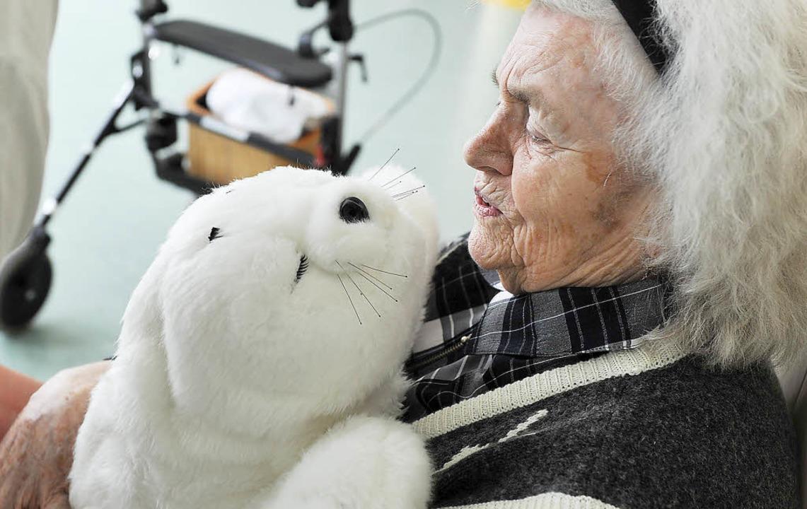 Eine demenzkranke  Frau hält einen Plü...zu erreichen, die unter Demenz leiden.  | Foto: dpa