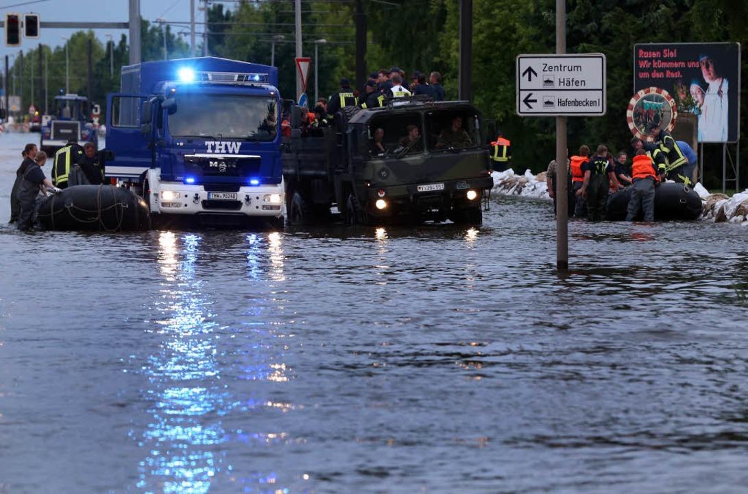 Bundeswehrsoldaten und das THW kämpfen gegen die Wassermassen in Magdeburg.  | Foto: AFP