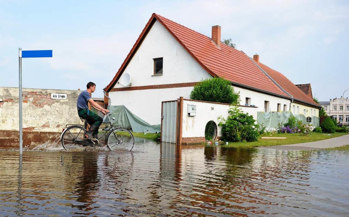 Ein Radfahrer fährt in Wust (Sachsen-A...e von Hochwasser überfluteten Straßen.  | Foto: dpa