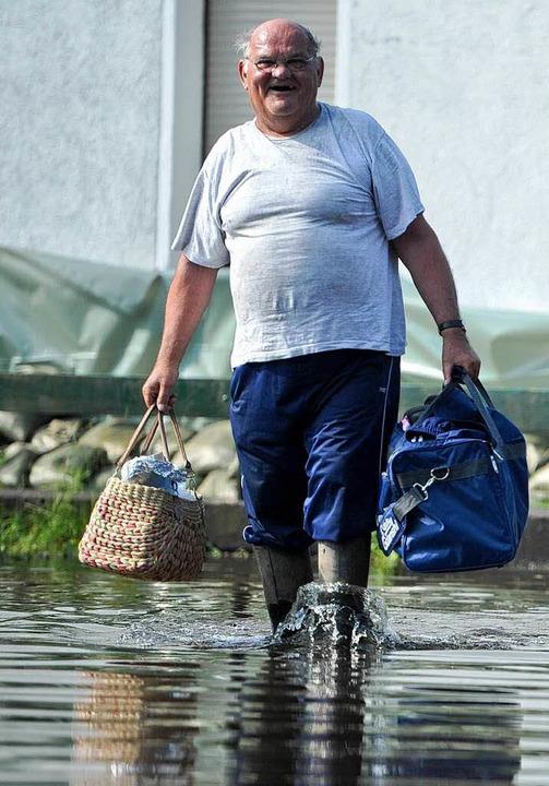 Ein Mann läuft  in Wust  mit Gepäck du...wohner verlassen das überflutete Dorf.  | Foto: dpa