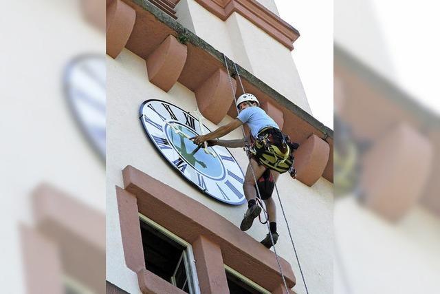 Industriekletterer montiert neues Zifferblatt der Turmuhr