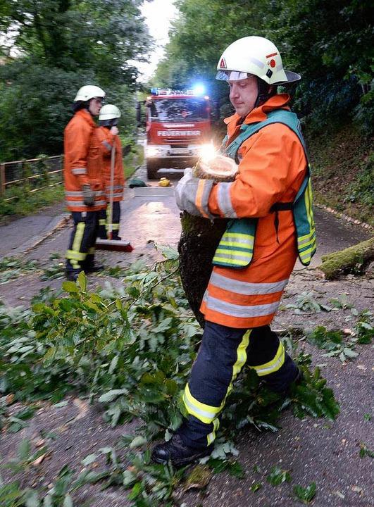 Feuerwehrmänner entfernen Bäume, die auf eine Straße in Freiburg gefallen sind.  | Foto: dpa