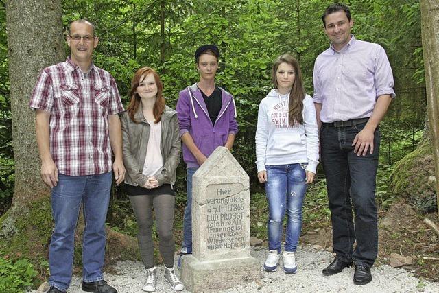 Jugendliche restaurieren einen alten Gedenkstein