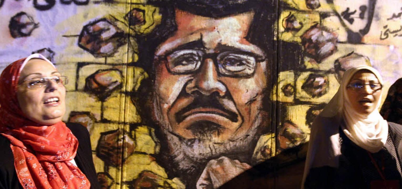 Frauen demonstrieren vor einem Wandgem...hen Präsidenten Mohammed Mursi zeigt.   | Foto: DPA