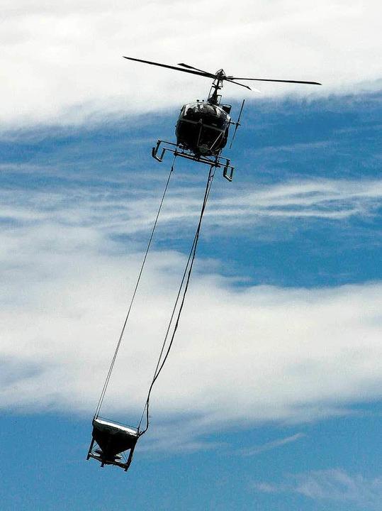 Per Hubschrauber bringt die Kabs den W...nulat über Gewässern und Wäldern aus.   | Foto: dpa