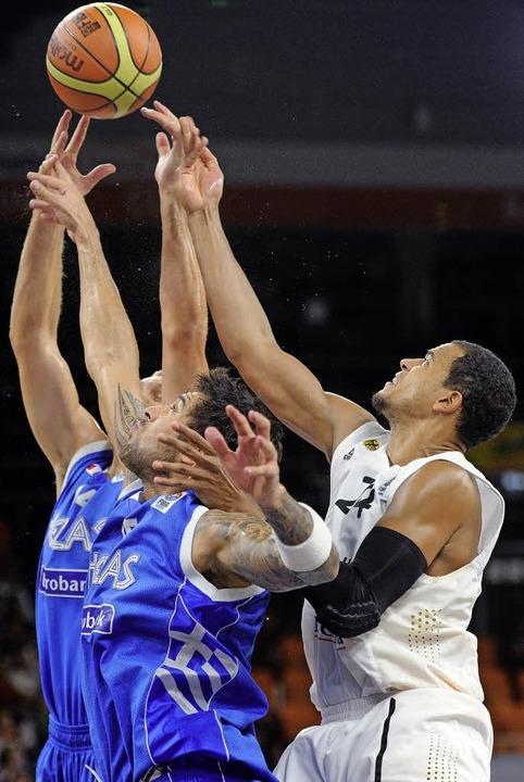 Arme hoch: Die Griechen  Michael Bramo...en Deutschen Alex King um den Ball.     | Foto: dpa