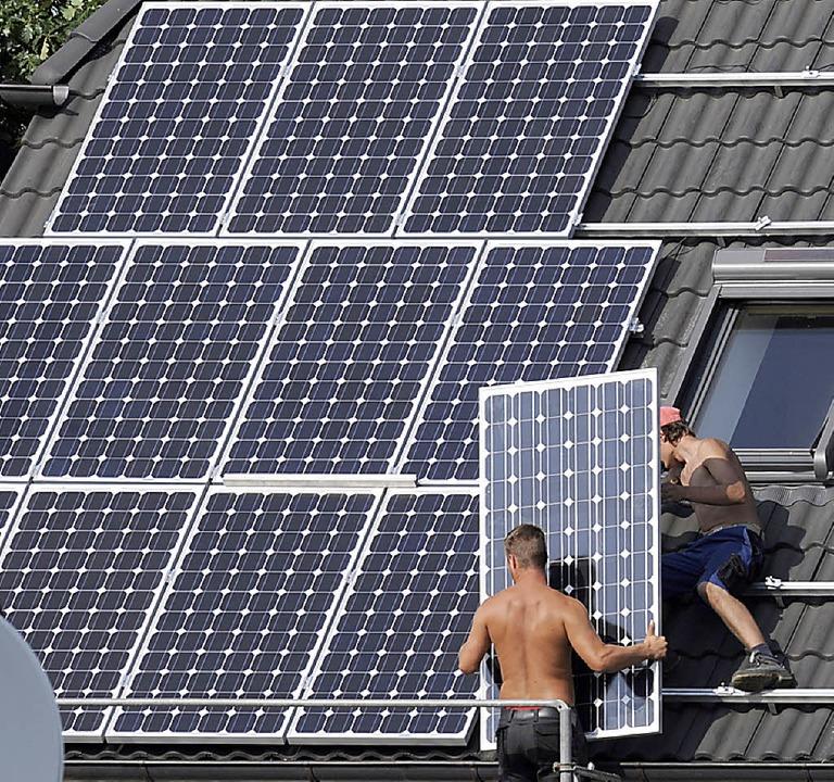 Auf ein Einfamilienhaus wird eine Photovoltaikanlage installiert.   | Foto: dpa