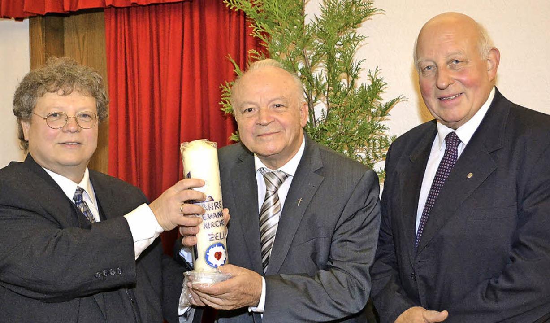 Gelebte Ökumene: Vakanzpfarrer Peter H... Übergabe einer Kerze mit Lutherblume.    Foto: Paul Berger