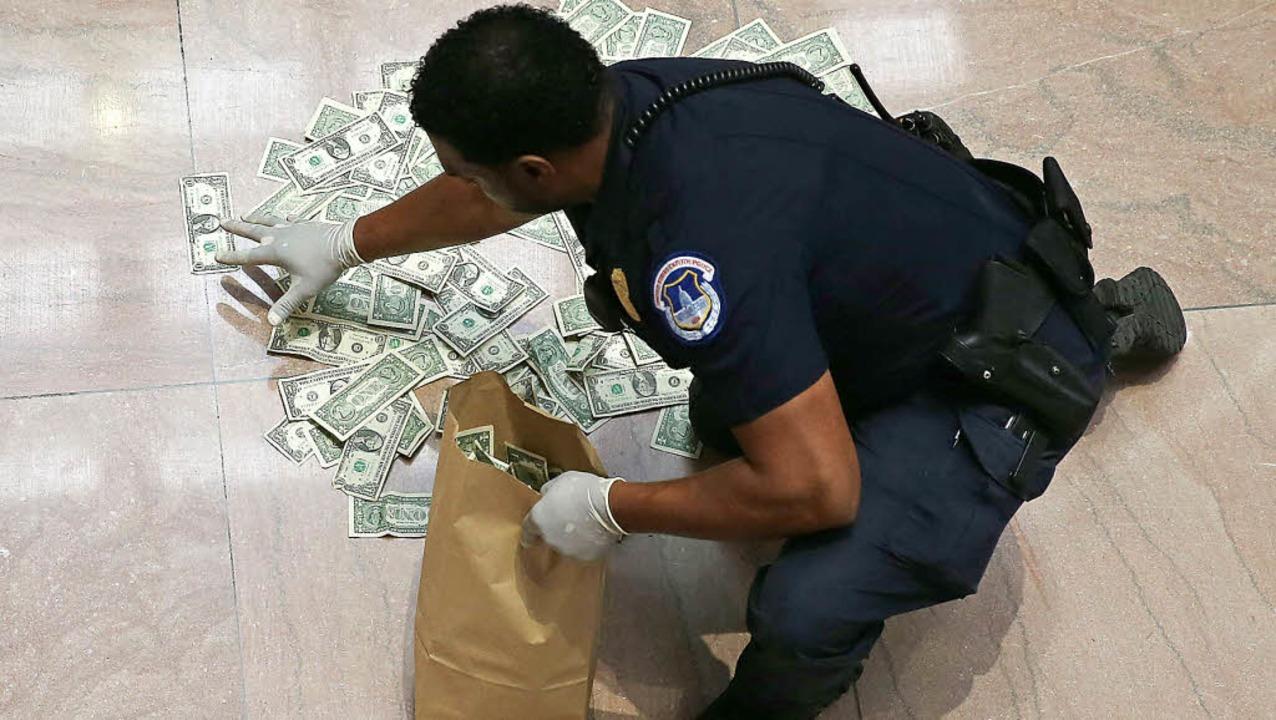 Schnell weg mit den Dollarnoten, sagt ... über den Haushaltsstreit zu äußern.      Foto: AFP