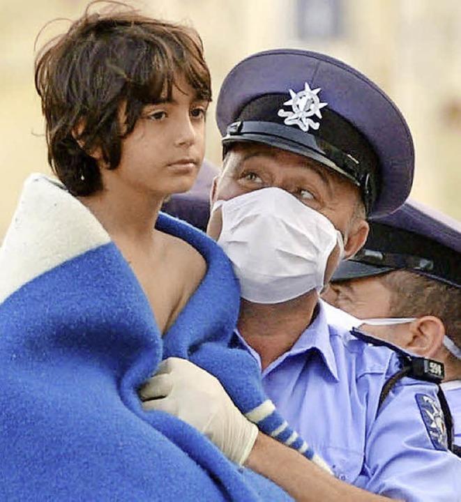 Ein maltesischer Polizist hält ein gerettetes Flüchtlingskind.  | Foto: AFP