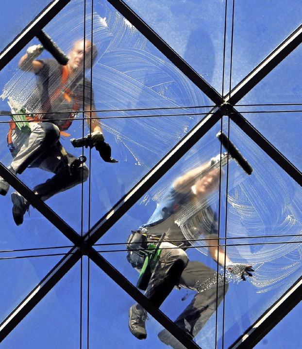 Schwindelfrei müssen Gebäudereiniger s...liegt der Einsatzort in luftiger Höhe.    Foto: DPA/Tolsdorf (2)