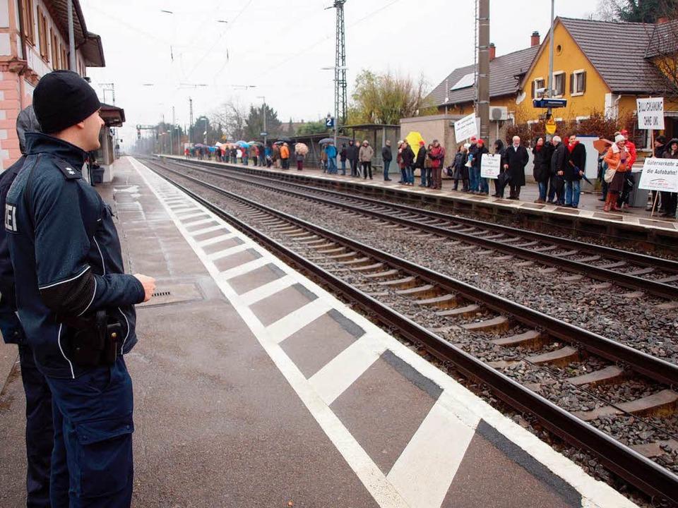 Menschliche Lärmschutzwand: Die Polize...monstranten am Bahnhof in Herbolzheim.  | Foto: Michael Haberer