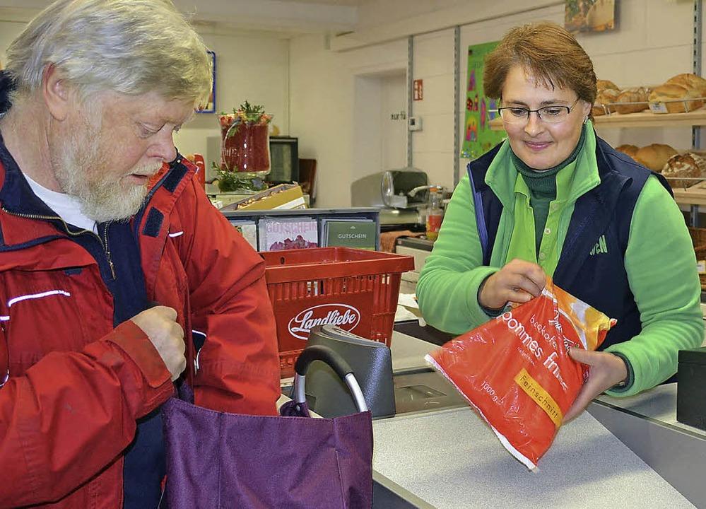 Barbara Knörzer, Leiterin des Dorfladens, mit einem Kunden.  | Foto: Schilling