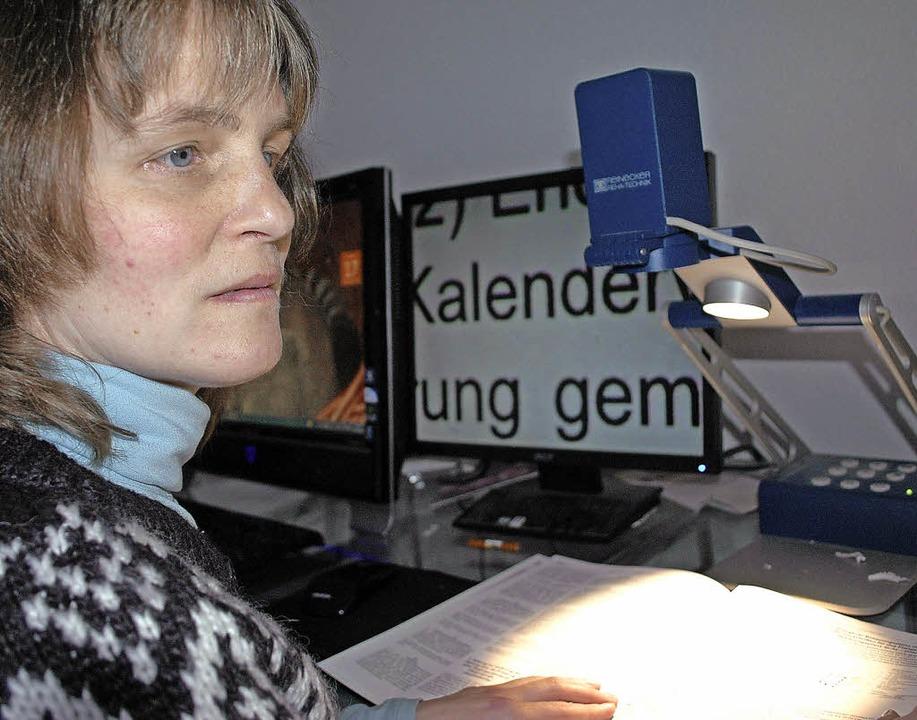 Anne Tesch sitzt vor dem Lesegerät, da...rößert auf einen Bildschirm überträgt.    Foto: annemarie zwick