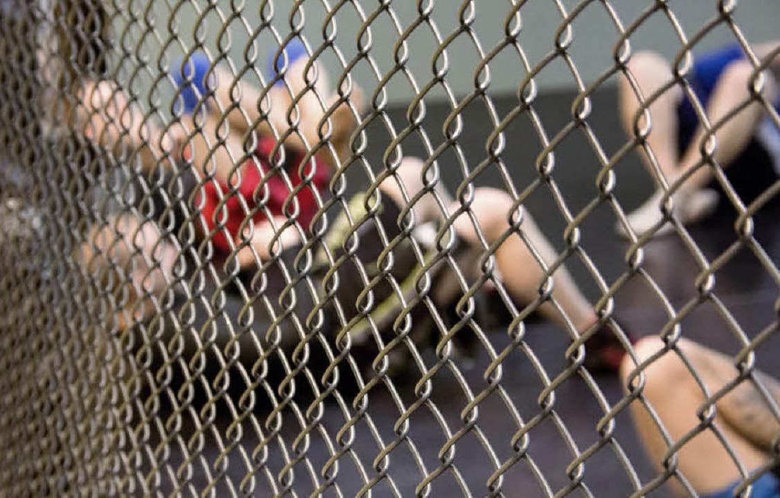 Sit-Ups hinterm Maschendraht: MMA-Kämpfe finden in einem Käfig statt.  | Foto: Christoph Koch