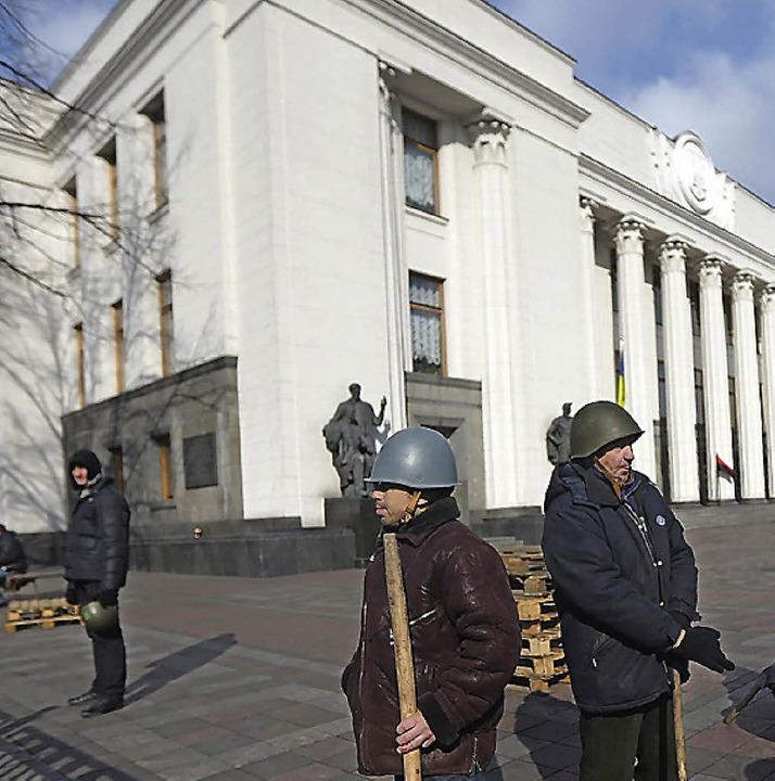 Janukowitsch-Gegner bewachen das Parlament in Kiew.   | Foto: dpa