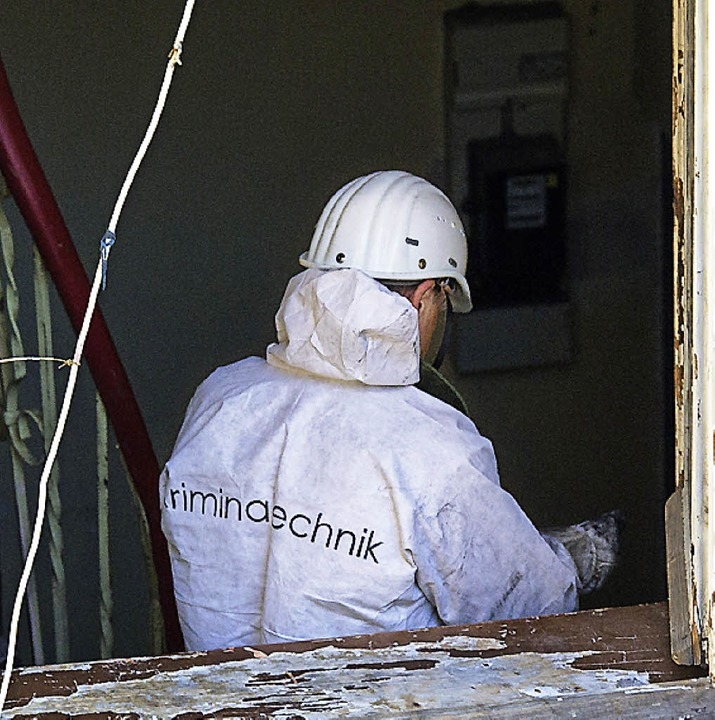Ein Polizist untersucht Brandspuren in der Wohnung.   | Foto: dpa
