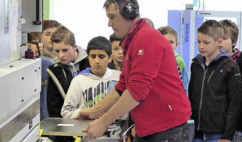 Die Technikschüler mit Firmenchef Jürg...hten einen Mitarbeiter am Bandautomat.    Foto: RAG