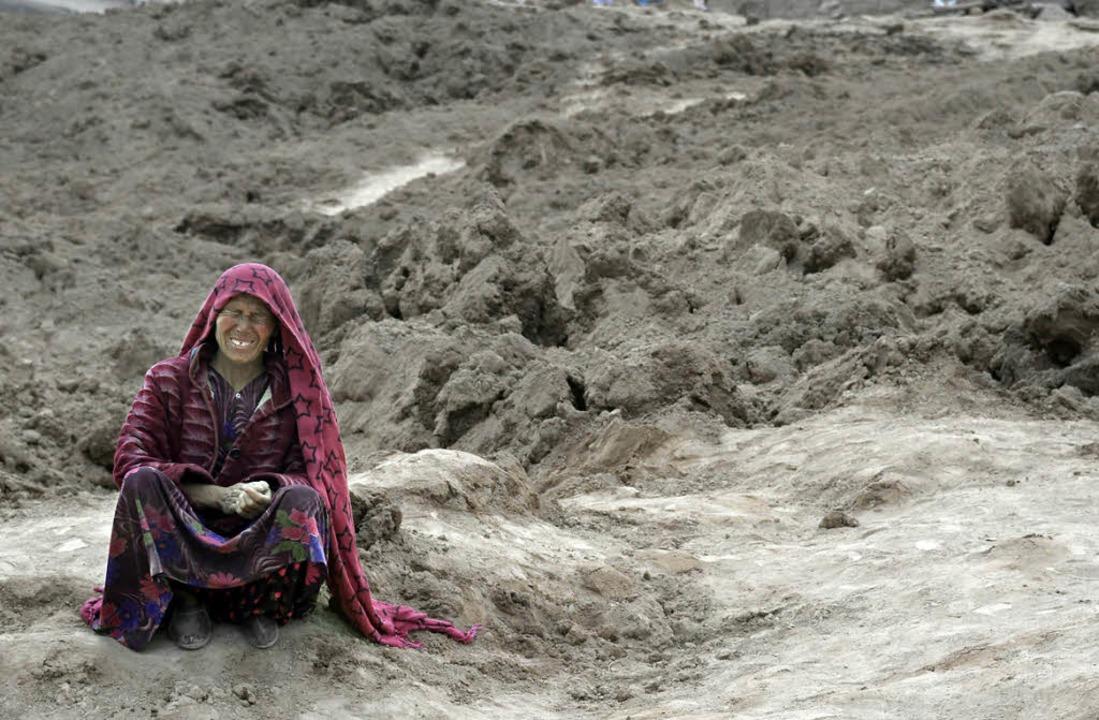Eine Überlebende sitzt weinend auf dem...er dem ihr Heimatdorf begraben liegt.   | Foto: AFP