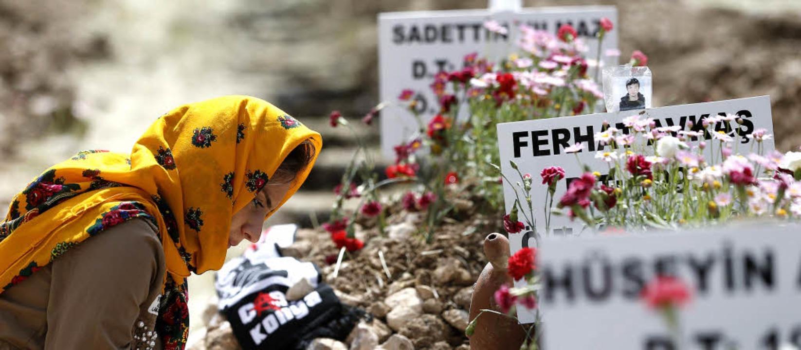 Eine Frau trauert an der langen Grabre...toten Minenarbeiter ausgehoben wurde.   | Foto: dpa