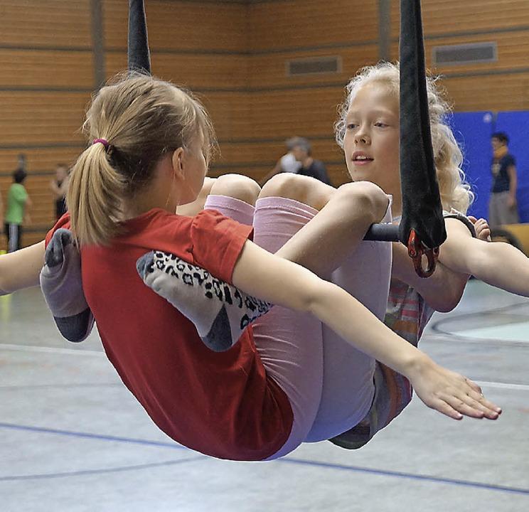 Hier üben zwei  Schülerinnen ihr Kunststück am Trapez.    Foto: Susanne Ehmann