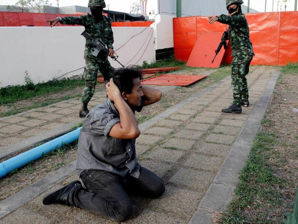 Ein Soldat befiehlt einem Regierungsanhänger, hinzuknien.  | Foto: dpa