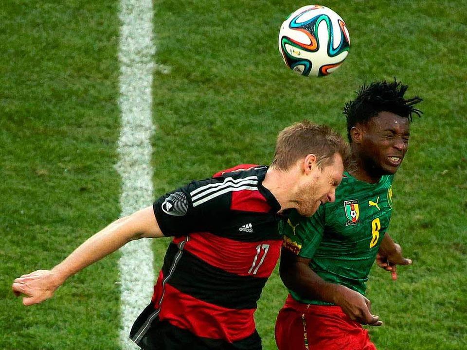 Der Deutsche  Per Mertesacker im Kopfb... mit  dem Kameruner Benjamin Moukandjo  | Foto: dpa