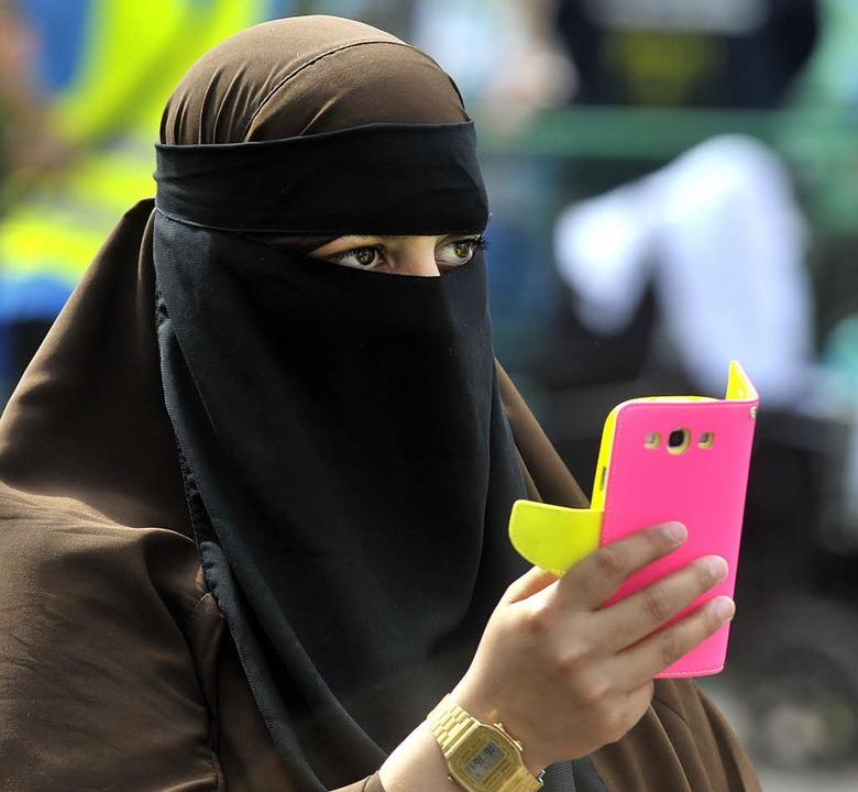 Eine Teilnehmerin der Kundgebung nimmt...e der Prediger mit dem Smartphone auf.    Foto: Michael Bamberger