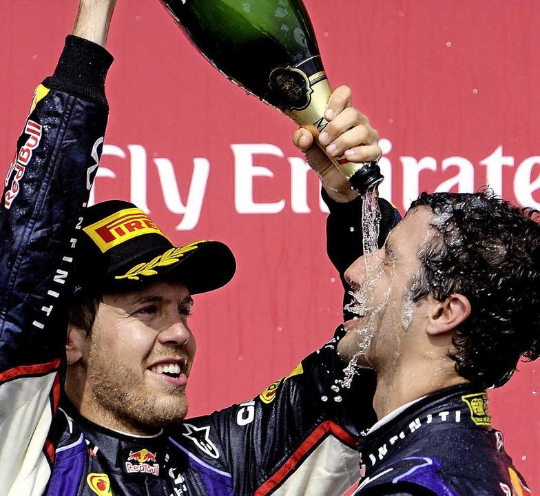 Daniel Ricciardo (rechts) lässt sich vom Dritten Sebastian Vettel begießen.     Foto: DPA