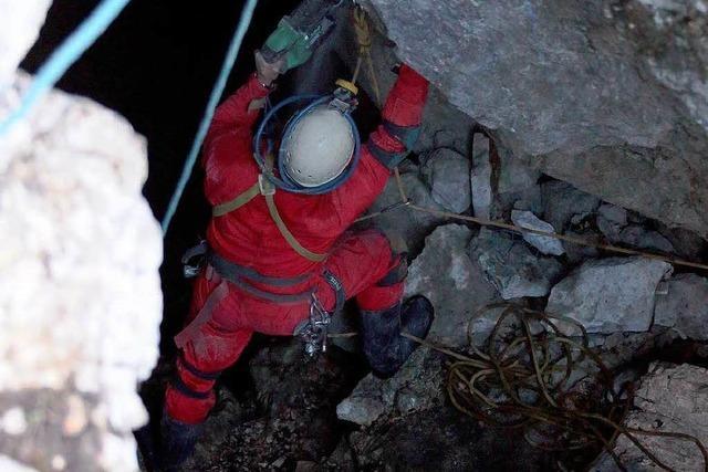 Rettungsteam mit verletztem Höhlenforscher vor steilem Aufstieg