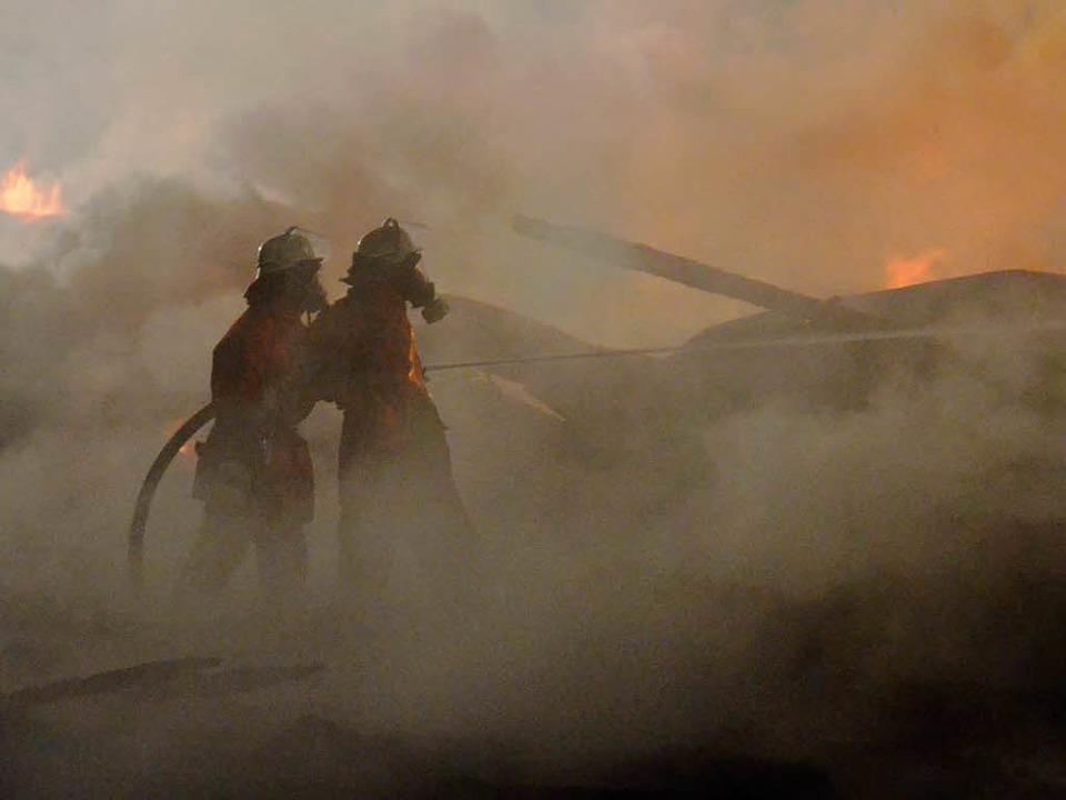Atemschutzträger bekämpfen das Feuer i...tlerweile niedergebrannten Lagerhalle.  | Foto: Sebastian Barthmes