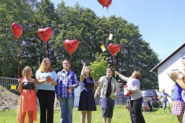 Abschlussfeier mit roten Luftballons
