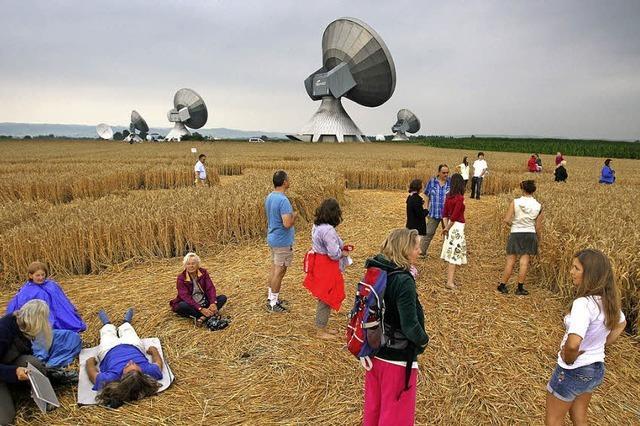 Esoterik-Anhänger pilgern zu einem Kornkreis in einem Feld