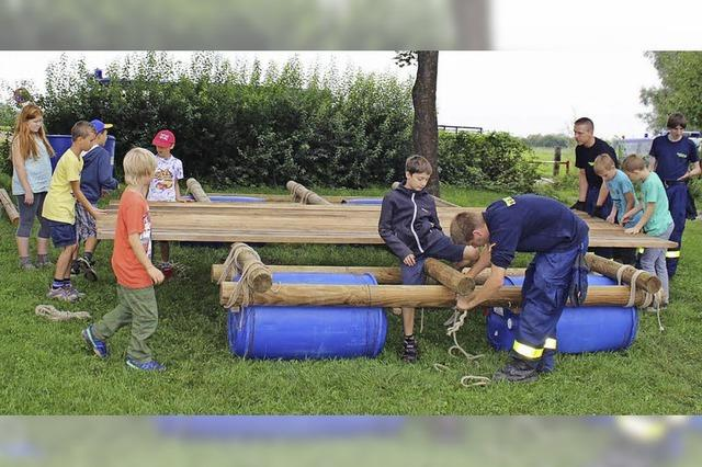 Kinder und Jugendliche bauen ein Tonnenfloß
