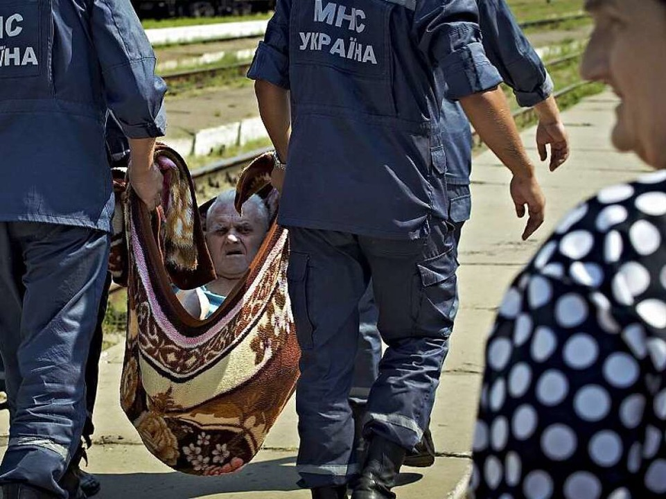 Ukrainische Rettungskräfte tragen in der Nähe von Lugansk  einen Flüchtling.    Foto: dpa